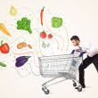 Businessman with shopping cart with vegetables — Stock Photo #71032737