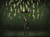 Businessman standing with umbrella in dollar bill rain concept — Stock Photo