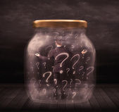 Businessman locked into a jar with question marks concept — Stock Photo
