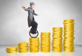 Business man riding monocycle up on coin graph — Stock Photo