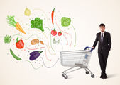 Businessman with shopping cart with vegetables — Stock Photo