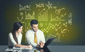 Business couple with business diagrams — Stock Photo