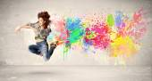 Happy teenager jumping with colorful ink splatter on urban backg — Stock Photo