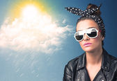 Young person looking with sunglasses at clouds and sun — Stock Photo
