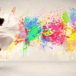Happy teenager jumping with colorful ink splatter on urban backg — Stock Photo #72712487