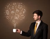 Businessman holding a white cup with social media icons — Stock Photo