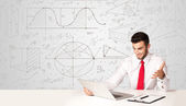 Businessman with business calculations background — Stock Photo