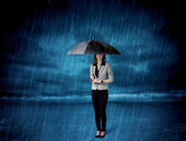 Business woman standing in rain with an umbrella — Stock Photo
