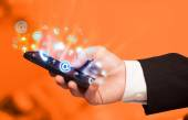Business man holding smart phone with media icons — Stock Photo