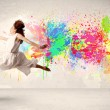 Happy teenager jumping with colorful ink splatter on urban backg — Stock Photo #73673595