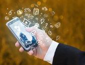 Ruka držící smartphone s mediální ikony a symboly — Stock fotografie