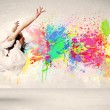 Happy teenager jumping with colorful ink splatter on urban backg — Stock Photo #76220529