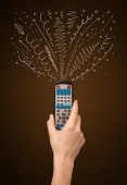 Hand with remote control and curly lines — Stock Photo