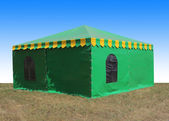 Green very big  tent in the field — Stock Photo