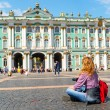 Young female tourist in front of the Winter Palace in St. Peters — Stock Photo #55814125