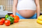 Pregnant woman with fresh vegetables in the kitchen — Stock Photo
