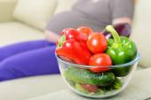 Fresh vegetables on the couch next to a pregnant woman — Stock fotografie