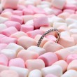 Wedding ring on pink and white mini marshmallows — Stock Photo #62013345
