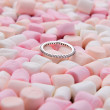 Wedding ring on pink and white mini marshmallows — Stock Photo #62013509