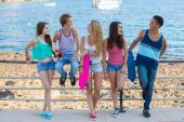 Group of diverse mixed race teens hanging out at beach.  — Stock Photo