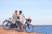 Tourists with bikes looking at map — Stock Photo