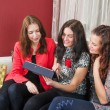 Three young women friends chatting at home and using laptop to l — Stock Photo #66386969