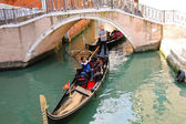Gondolier sailing with tourists in a gondola along one of the ca — Stock Photo