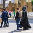 Постер, плакат: Actor in costume Darth Vader walking down the street and attract