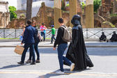 Actor in costume Darth Vader walking down the street and attract — Stock Photo