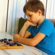 Pensive boy during a game of checkers — Stock Photo #56217091