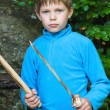 Serious kid with a wooden sword on stone — Stock Photo #62042765