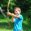 The kid shoots a bow in the park — Stock Photo #63858187