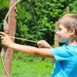 The kid shoots a bow in the park — Stock Photo #63858189