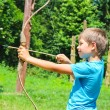 The kid shoots a bow in the park — Stock Photo #63858191