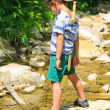The kid plays near a mountain stream — Stock Photo #63858193