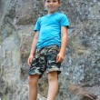 Smiling boy standing near the steep rock — Stock Photo #63858195