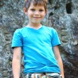 Smiling boy standing near the steep rock — Stock Photo #63858217