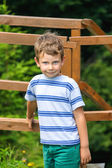 Smiling boy standing near the a wooden fence — Stock Photo