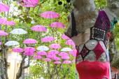 Knitted clothes on trees and umbrellas decorate street in the r — Stock Photo