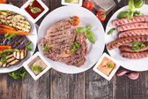 Grilled beef, sausages and vegetables — Stock Photo