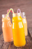 Fruit juice in glass bottles with straw — Stock Photo