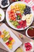 Sliced fruits on plates and dip of chocolate — Stock Photo