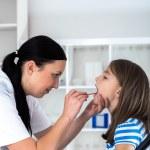 Doctor check throat of little girl — Stock Photo #58828197