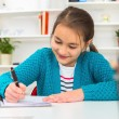 Beautiful girl working on her school project at home — Stock Photo #64549973
