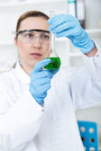 Chemist woman testing sample of liquid in laboratory — Stock Photo