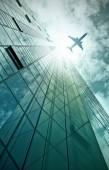 Plane flying over office building — Stockfoto