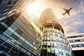 Plane flying over modern office tower — Stock Photo