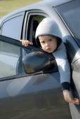Cute boy looking out of the car — Stock Photo