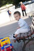 Baby boy sitting on bench — Stock Photo