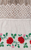 Fabric with embroidery flowers on the old wood — Stock Photo